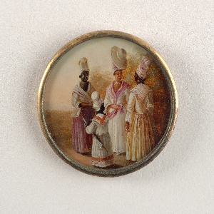 Button depicting scene of four figures in a landscape. Three women and a child wearing dresses. At center a light-skinned woman in jewelry and large turban topped with a sunhat.