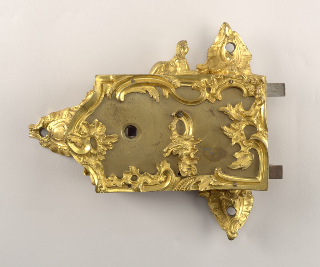 Rectangular brass lock box overlaid with chiselled rocaille ornament. At top, a sphinx.