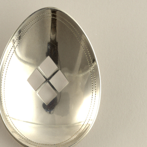 Oval bowl with intersected diamond pattern cut-out at center of bowl outlined by double row of stippling. Join with three horizontal bands, straight shaft (with three horizontal bands) widening to form handle with three horizontal lines and pointed end with double outline of stippling.
