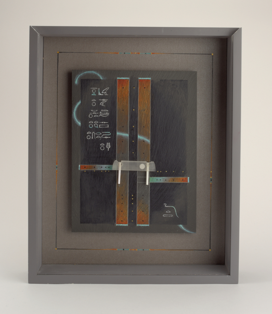 Gray rectangular box with Plexiglass front panel that slides up to allow access to decorated slate panel with mount for brooch.