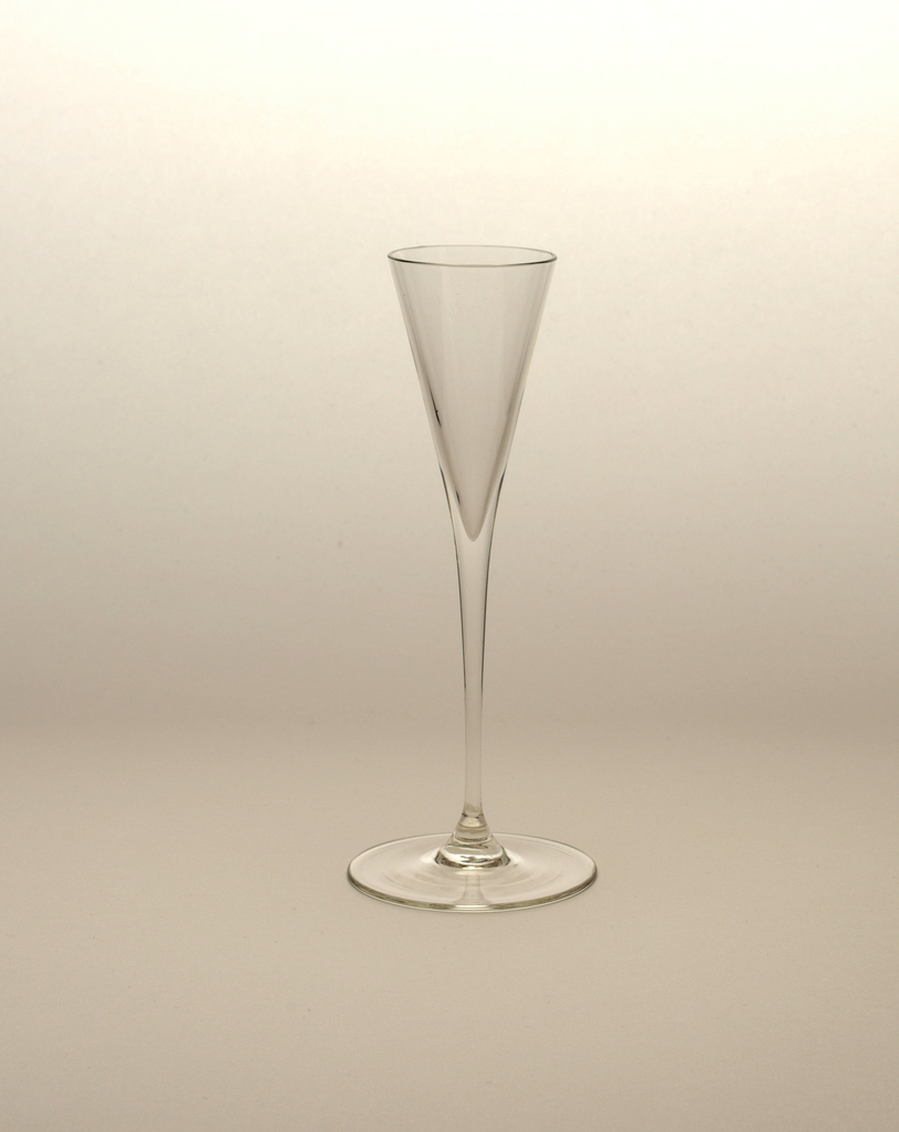 """Thin blown crystal (""""Muslin glass"""") cordial glass with triangular body and thin stem, terminating at a large round base."""