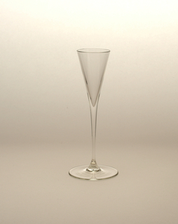 "Thin blown crystal (""Muslin glass"") cordial glass with triangular body and thin stem, terminating at a large round base."