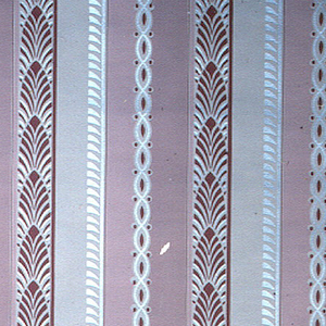 Wine red, pink, cream, and metallic silver stripe of cables and overlapping leaf design on a cream ground.