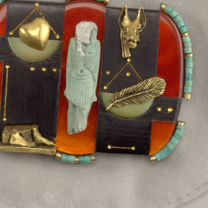 Roughly rectangular form, the ebony and carnelian surface with applied fragment of Egyptian faience figure in center, flanked by gold heart in scale above gold feet on left, jackal's head holding scale with feather on right; turquoise beads applied along left and right edges, and center top and bottom edges.