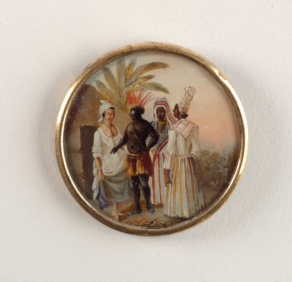 Circular form with painted scene depicting light skinned woman on left in white, low cut bodice with mid-length, ruffled sleeves, loose white overskirt, longer light blue underskirt, barefeet, white scarf on head, and long, tied black ribbon around her neck. She lifts skirts slightly while gazing at black man to her right; he wears short orange and brown skirt, possibly feathered, with brown strap draped diagonally across his bare chest and tall, orange feathered headdress. His left hand is on his hip while he points downward with his right hand as he gestures to the lighter skinned woman. Behind him to the right are two black women: one wears long orange, white, and black vertically striped skirt, scarf with black and orange stripes, draped head scarf with orange stripes, and gold beaded choker around neck; second woman at extreme right with her back turned to viewer wears long gold, white, and black vertically striped skirt, orange and white scarf draped over shoulders, white blouse with 3/4 length sleeves, tall orange and white turban on her head, and white pendant earrings; both women gaze at the other two figures. Landscape of palms and other plant life in background, as well as indigenous architecture at rear left. Sky painted in pale blue and orange tones. Painting protected by domed glass and framed in gilded metal. Plain metal loop attached to center of reverse side.