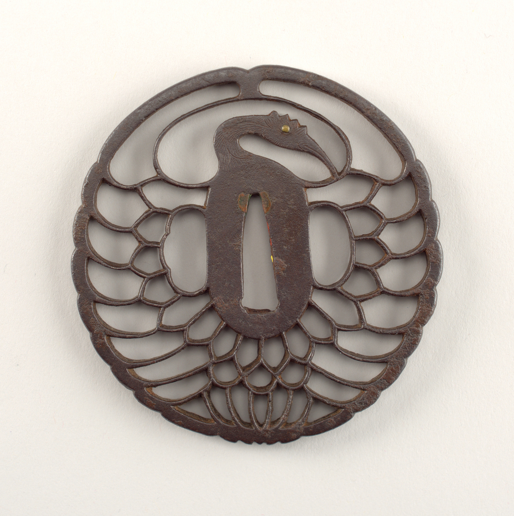 This Kyo-sukashi (Kyoto openwork) style tsuba takes the form of a tsuru maru (crane circle). At the center is the nakago-ana, an opening through which the sword passes, with traces of sekigane (plugs added to fit the tsuba to a sword) made of shakudo (a soft copper and gold alloy). The surrounding seppadai (flat oval area) forms the body of the crane; it is elegantly long and narrow, with a migaki (burnished) surface. The head of the crane has kebori (line carving). Flanking the body are ryo-hitsu, openings for the kozuka (utility knife) and the kogai (skewer tool). At right is sashi ura, the side which faces the blade, whose opening takes the hangetsu-kei (half moon) shape. Opposite is sashi omote, the side which faces the sword hilt; its tri-lobed opening is of the suhama type, and symbolically represents the coastline of Horai, the holy island of the Immortals. The surrounding openwork forms symmetrical feathers with a sense of movement.