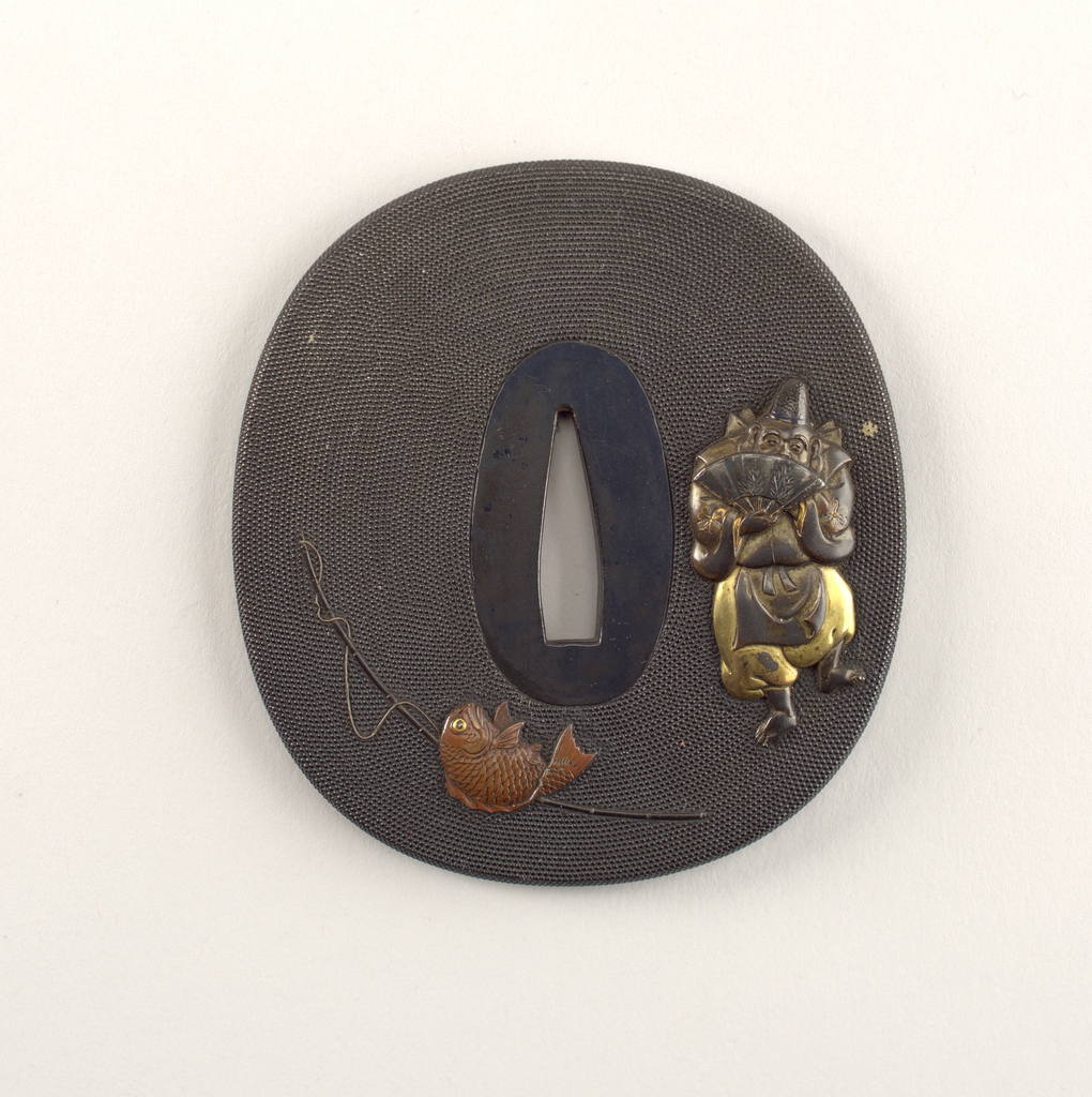 This iron and shakudo (copper and gold alloy) tsuba is oval in shape and has a kakunikumimi (high relief rim). The surface shows nanako (a punched pattern of dots) and is decorated with iroyo takabori  (high relief carving), and taka zogan (high relief inlay). The motif is a daishō (big -little) type scene with Ebisu, the god of fishermen and luck, with a sea bream. At the center is the nakago-ana, an opening through which the sword passes. Surrounding this is the seppadai, a flat oval area that is migaki (burnished).