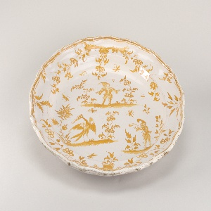 Circular form with shaped rim. Monochrome ochre decoration shows Callot-style figures on staggered terraces, and allover scattered florals.