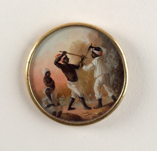 Button depicting scene with four figures in a tree-filled landscape, wearing Western garments; three wear turbans while the fourth wears a scarf on head; two are shirtless and two are training with wooden sticks.