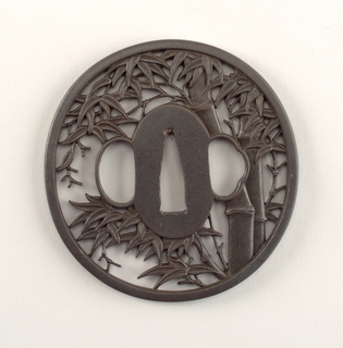 Circular form with openwork decoration of bamboo foliage and trees surrounding three openings in center for sword and two fittings.
