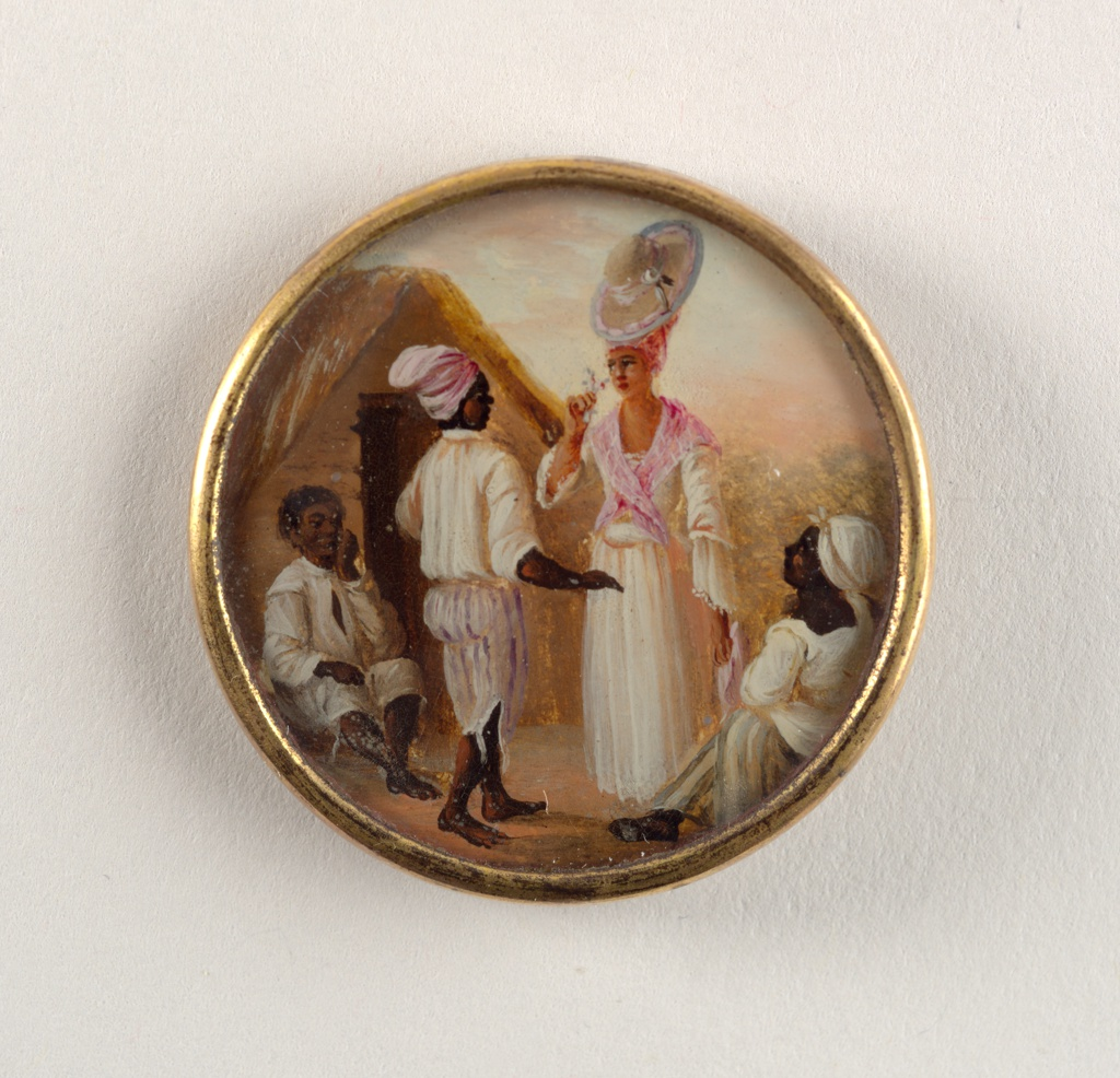 Button depicting scene of four figures outside before a thatched hut. At center, a man in striped pants and white shirt faces a woman in a dress with a pink scarf who smells a flower. Seated man and woman on either side stare up at central couple.