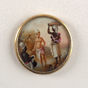Button depicting scene of three figures in a landscape with a body of water. A light-skinned woman, nude but for a shawl around her waist, stands before two dark-skinned bare-breasted women. On the left, woman is crouching holding a white handkerchief; on right standing woman with child tied to her back and carrying a package on her head.