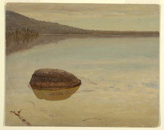 View of a wooded shore across a lake.  The shore rises toward the left.  Part of a dead branch and a boulder are shown in the foreground.