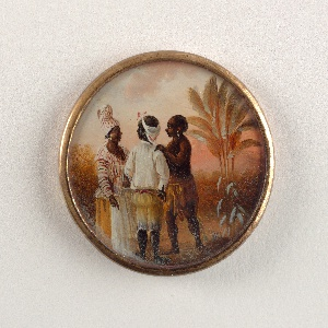 Button depicting scene of three conversing figures in a landscape with palm trees. A woman dressed in a striped shirt and turban, a man facing the woman with back to viewer in striped pants and white shirt, and a second man wearing native West Indies dress in skirt and headband.