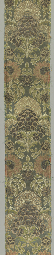 Blue-green satin with vertical rows of large symmetrical floral palmettes between columns of smaller palmettes, large flower heads, feathery leaves, serpentining lace, in tarnished silver, pink, yellow, white, and green.