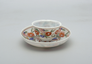 White glass with painted decoration.  Red and blue bird central figure on saucer.