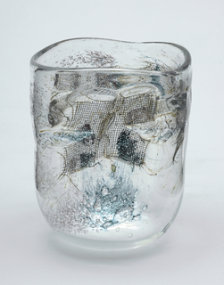 wide-mouthed vase of clear glass with some acqua-colored areas, air bubbles, and wire mesh inclusions.