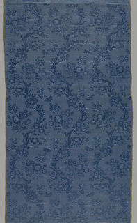 Continuous blue-on-blue pattern of three naturalistic curving floral vines with a bird perched on a flower placed side by side. Branches of flowers nestled on each curve of the vines.