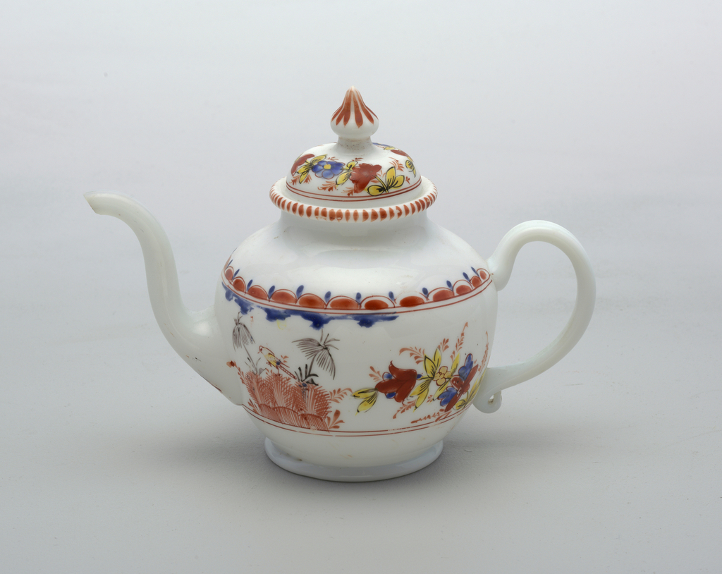 White glass with painted decoration.  A pair of painted red bushes with 2 umbrellas flank the spout of teapot