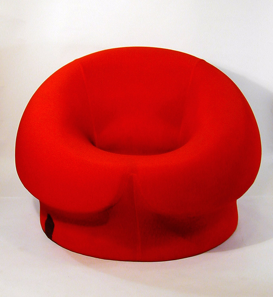 Red-upholstered, circular, thick foam form; cleft in bottom front of seat and low cylindrical base.