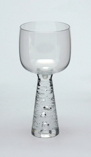 Clear glass with inverted tapered stem with horizontal ridged design.   Goblet