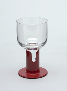 Clear glass cylindrical goblet inserted into red plastic stem.