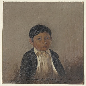 Portrait of a young boy facing right wearing a white shirt, black jacket and placed against a gray background.