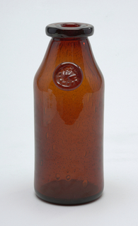 Rust colored glass.  Vase in the form of a milk bottle with glass medalion