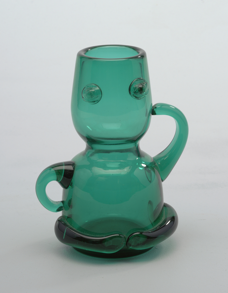 """Figural form transparent green bottle, double cup stack form with 2 arms, one at """"hip,""""  defined breast addition."""