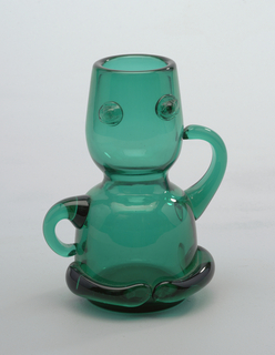 "Figural form transparent green bottle, double cup stack form with 2 arms, one at ""hip,""  defined breast addition."