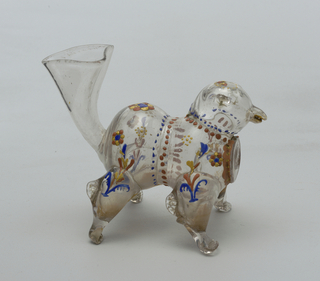 Clear glass creamer in the shape of a four-legged animal (dog?) Tail flares wide open to create a spout.  Some painted decoration