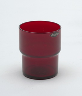 Nearly transparent red glass stepped cylindrical tumbler.
