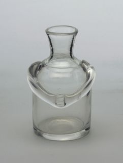 Clear glass vase.  Stout figural form with arms that cross at upper abdomen.