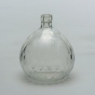 Clear glass bottle with long neck and bulbous body flatened on one side.  Body of bottle has faceted design in a hexongon pattern