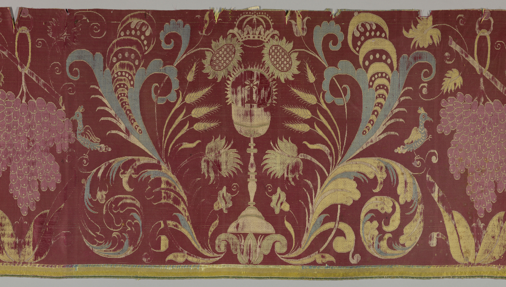 Religious motifs of grape, wheat, Host and paten in polychrome on red. Woven at right angles to the design.