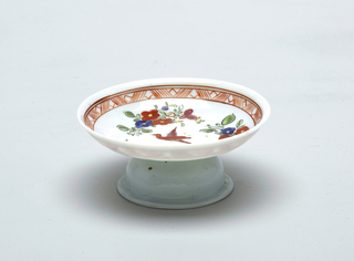 White glass footed bowl with slight blue cast.  Painted decoration.  Red hatch decoration around rim with red bird as central figure.