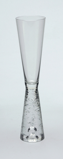 Clear glass with inverted tapered stem with horizontal ridged design.  Champagne
