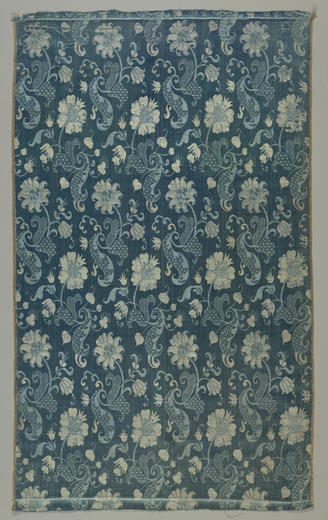 Length of blue silk with a pattern of flowers, leaves and scrolls in pink and light blue. Leaves and scrolls have diaper patterns.