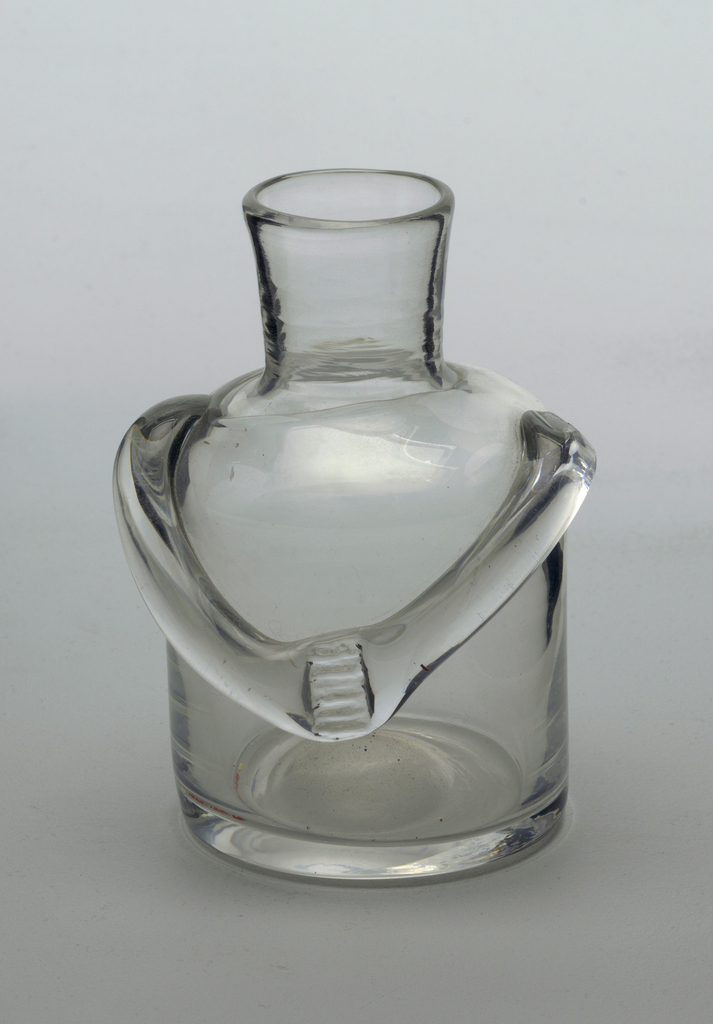 Clear glass bottle.  Stout figural form with arms that cross at upper abdomen.