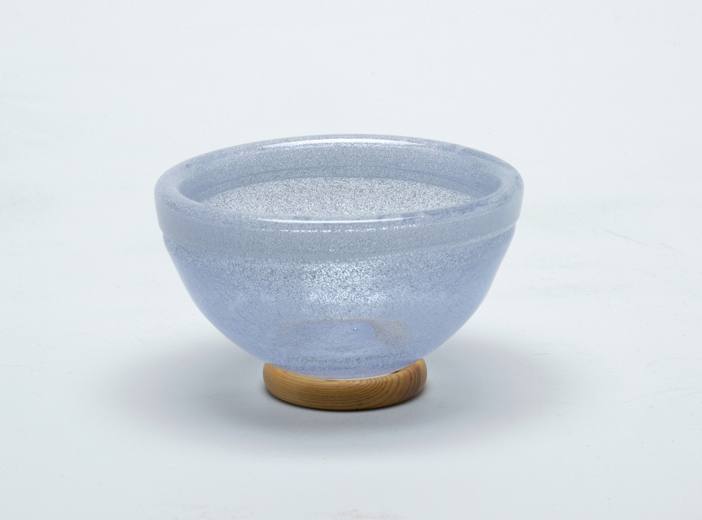 Pair of light blue glass bowls with wooden disk stands.