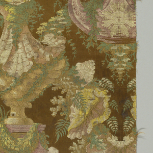 Large-scale rocaille design of a grotto with interlaced dolphins surmounted by a shell-form bearing another dolphin, alternating with symmetrical architectural form featuring a sun face, ram's heads, feathered head, all wreathed with foliage. In shades of green, yellow, pink, bluish-red, white, and tan on brown satin ground. Narrow cloth selvage with heavy warps.