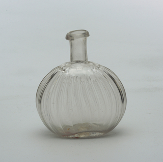 Clear glass bottle with long neck and flattened circular body.  The body of flask and a pressed glass ribbed pattern at a slight angle