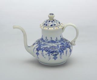White glass teapot with painted blue flower decoration.  Teapot has elongated neck.