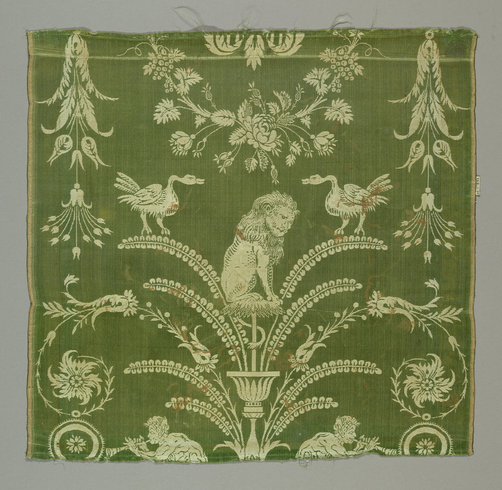 Green and white silk with a pattern of cherubs, garlands, piping fawns, and vase and fern motif. Seated lions and confronted swans.