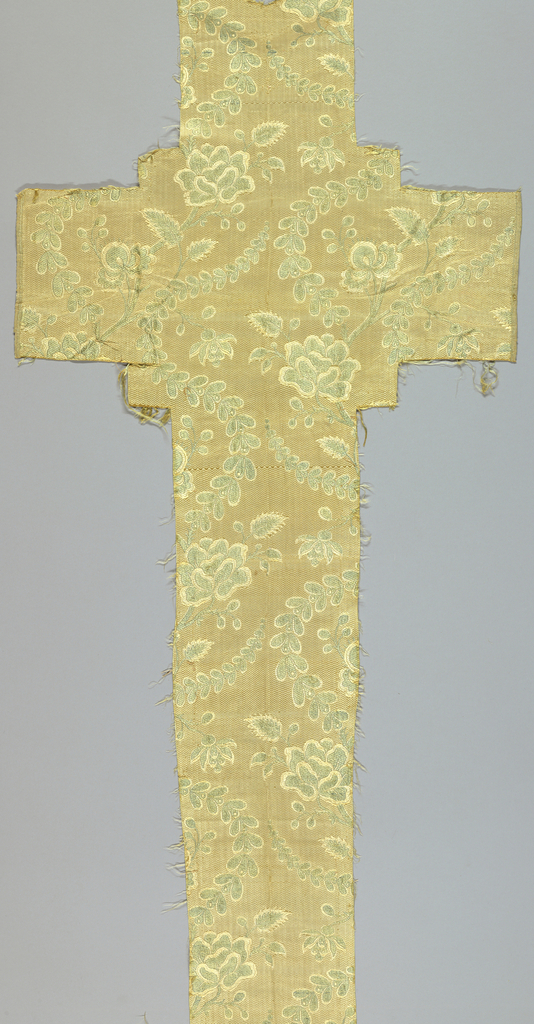 Cross-shaped fragment with patteen of serpentine floral and leaf shapes.