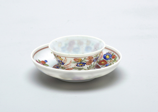 White glass with painted decoration of multi-colored flowers.  Saucer has 3 flowers at center
