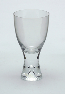 Clear glass with pronounced central air bubble in solid glass stem.  Red wine