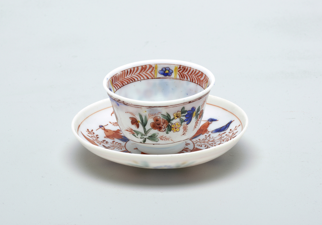 White glass with painted decoration.  Chinoiserie style figures decorate cup and saucer