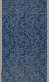 Skirt panel of deep blue silk with close-set, parallel serpentine flowering branches with small birds and large bouquets in between. Two selvedges, each with pink and yellow satin stripe.