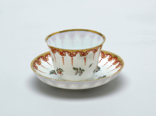 White glass with border around saucer and cup in a continuous arch-shape pattern.  Arches are orange/red with gilt trim.